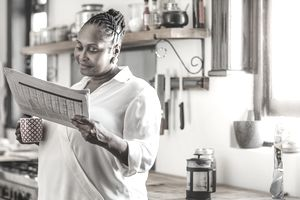 Woman reading a newspaper in her kitchen while holding a cup of coffee