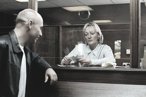 Man watching bank teller count out money