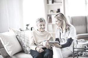 A caregiver sitting with an elderly woman on a bed discussing a medication