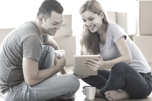 Couple seated on floor with coffee, looking at a tablet