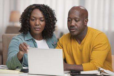African American couple using laptop together