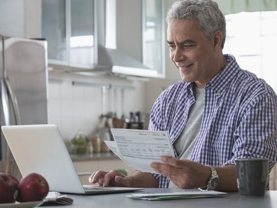 Grey haired man working on laptop with paper financial statements in one hand