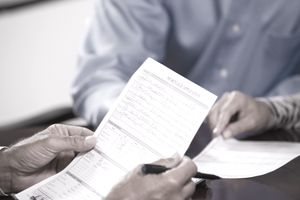 man holding mortgage application form and pen in his hands