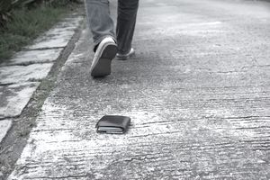 Person walking away from wallet they accidentally dropped