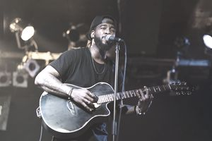 Black man playing acoustic guitar and singing on stage