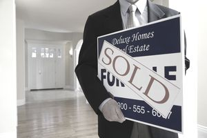 Realtor holding sold sign board in living room, mid section