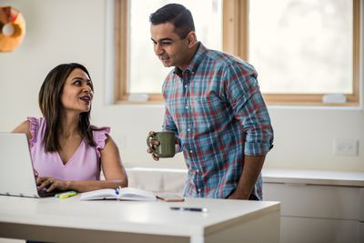 Spouses using laptop in kitchen
