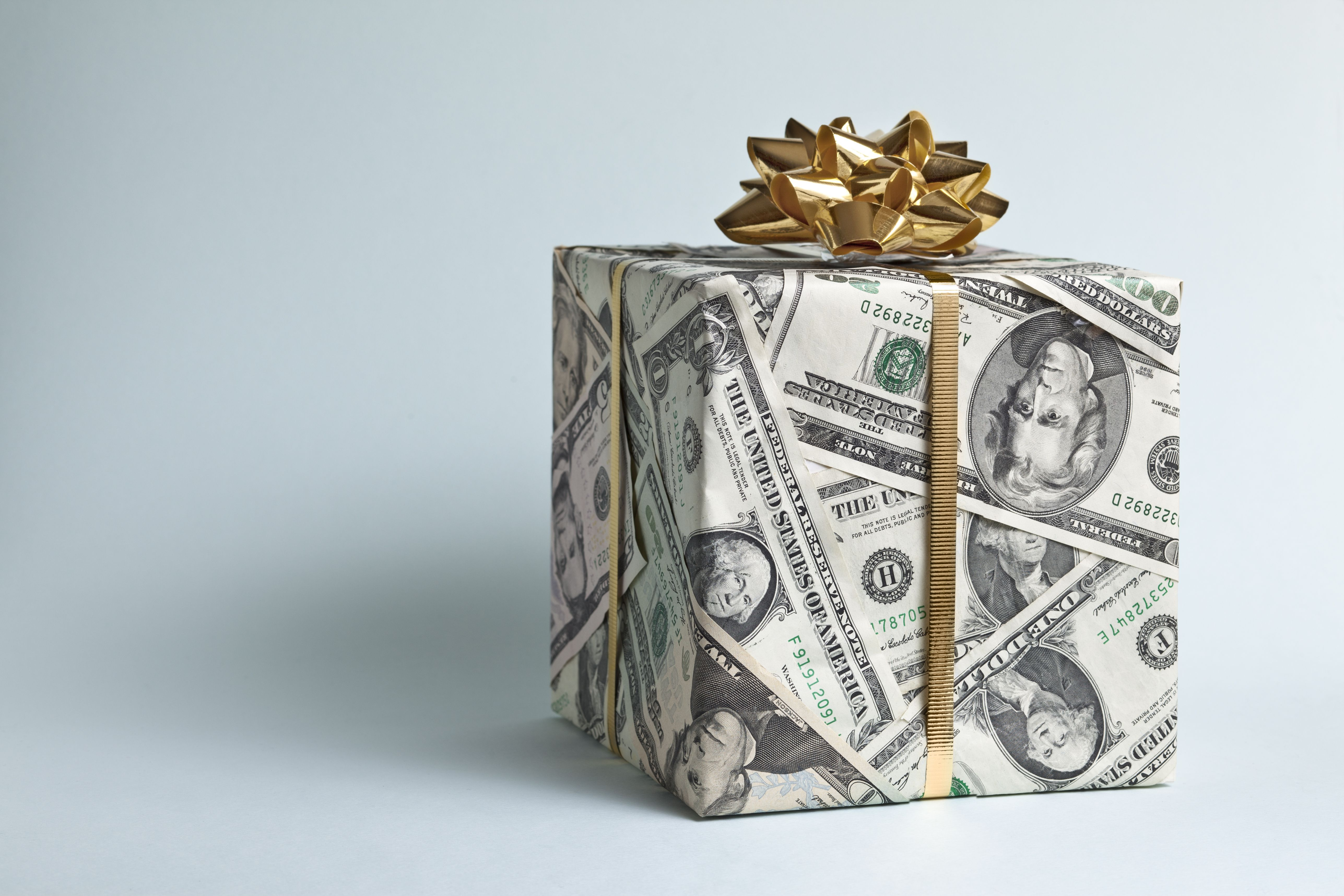 Gift wrapped in dollar bill gift wrap paper and tied with a gold bow
