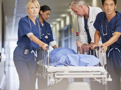 Emergency room professionals transporting patient on a gurney