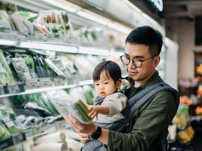 A young father shops for groceries.