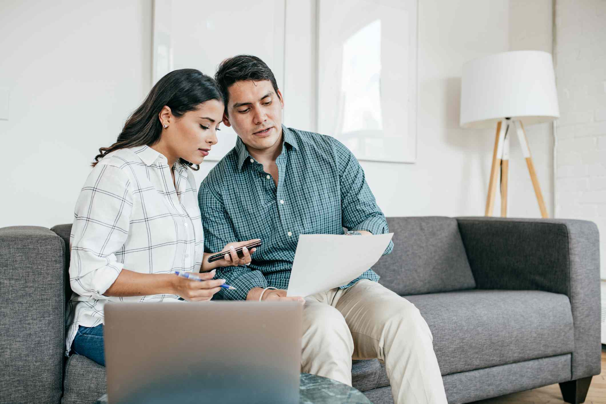 Couple on couch reviewing insurance documents