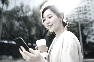 Confident young Asian businesswoman reading emails and drinking coffee on the go as she is walking down in the financial district in the city, against commercial buildings in the fresh morning