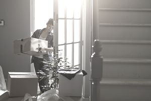 Woman carrying moving boxes into her new home