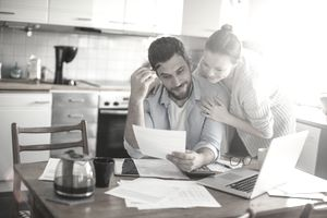 Husband and wife home budgeting at kitchen table