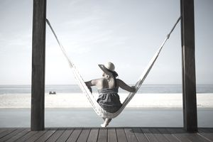 Woman sits in hammock facing the beach