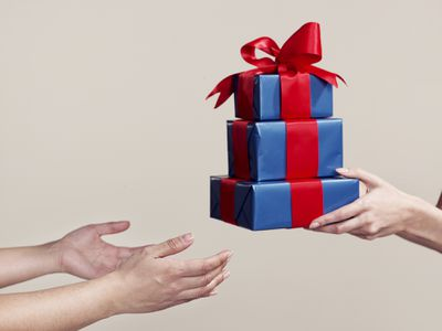 Female hands presenting three blue gift boxes with red ribbons