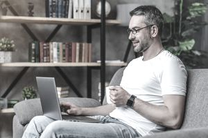 Man sitting on a couch with coffee mug in hand working on a laptop