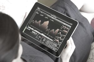 Woman checking stock market performance using financial application on an iPad tablet computer