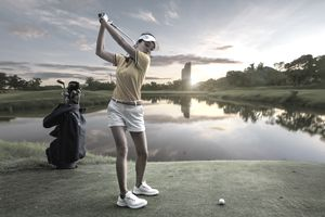 Asian woman swings at golf ball overlooking a lake