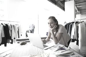 a business woman uses a laptop surrounded by clothes and sewing patterns