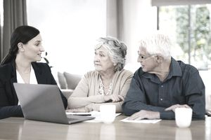 Dark-haired woman in blue suit explains something to older man and woman sitting next to her laptop.