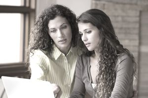 Mother and college-age daughter using laptop
