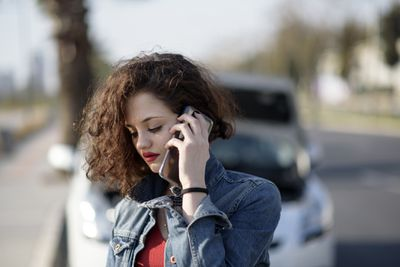 A driver calls their insurance company from the scene of an accident.