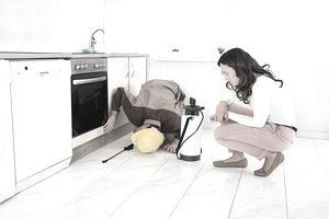 a man doing a pest inspection while a woman homeowner lucks on