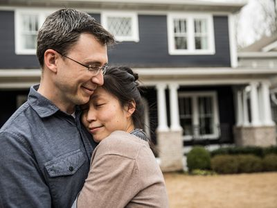 A couple embraces in front of their home.
