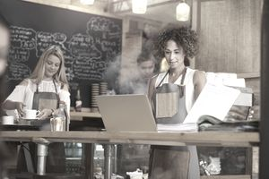 Coffee shop owner with laptop going over bills