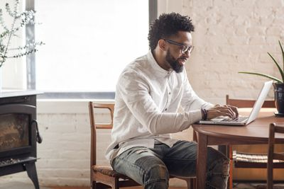 man in white shirt sitting on computer at wooden table