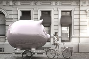 woman on a bicycle taking her Savings account piggy bank with her