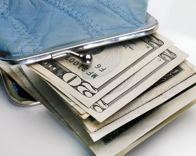 An open change purse with $20 bills sticking out of the opening