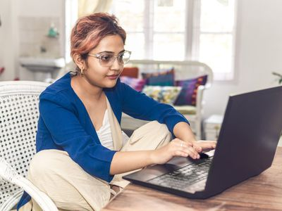 Young woman working on a laptop at a desk at home.