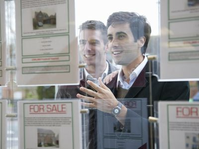 Couple looking into window with real estate listings