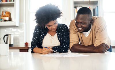 Couple reviewing papers together at their kitchen table