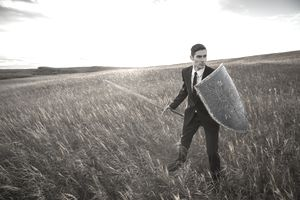Man in a suit in a field with a sword and shield