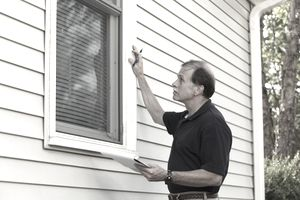 Home Inspector Looks at the Windows of a House for Sale