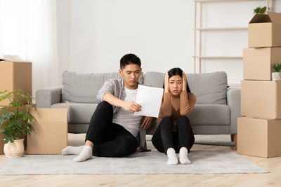 Young Asian couple sitting on floor amid cardboard moving boxes look shocked at a document