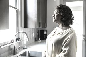 Senior woman looking out kitchen window