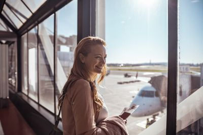 Woman looking out the window of an airport