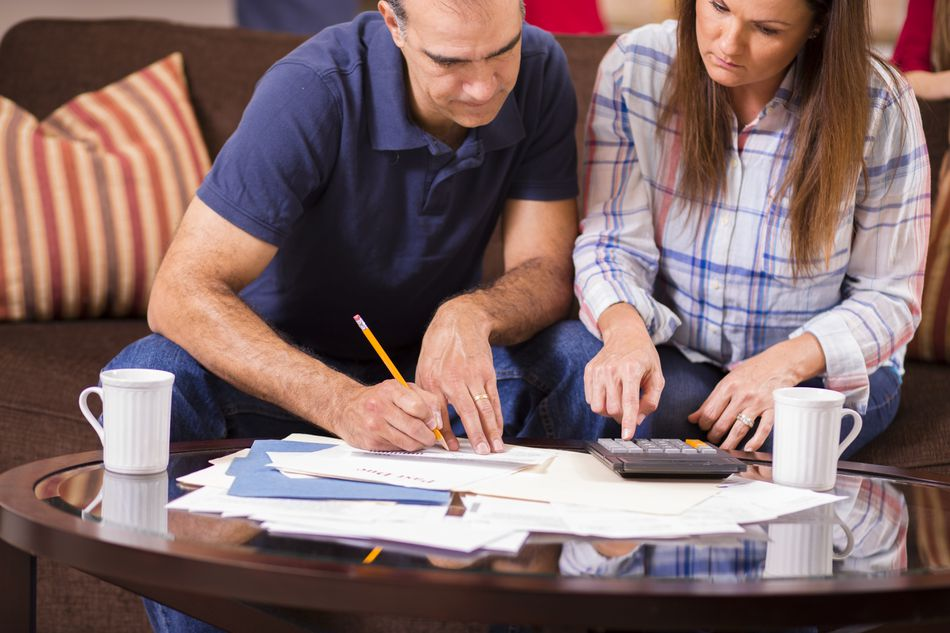 Couple seated on sofa working with paperwork and a calculator