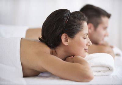Two People Lying Face Down on a Massage Table