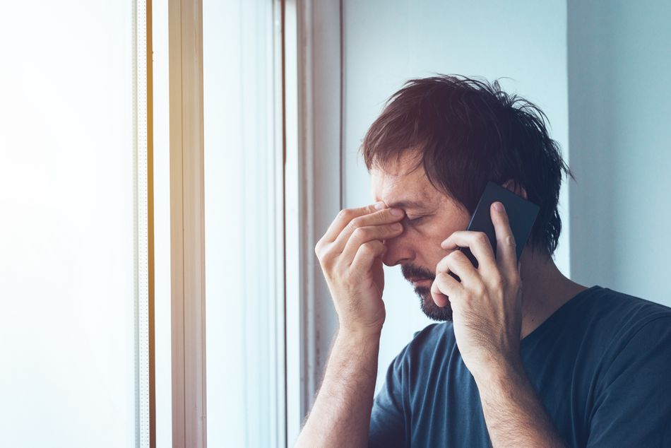 A worried man on the phone reporting identity theft to the FTC