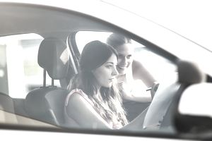 Teen driver looking concerned behind the wheel while her mother looks in the car window