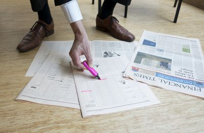 Business man marking stock in Financial Times spread out on floor