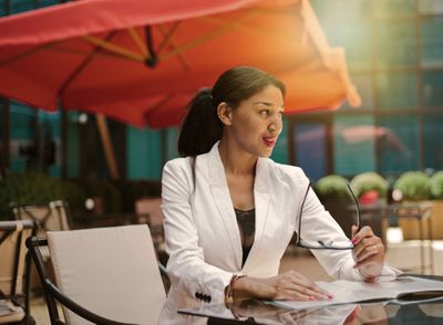 Smiling woman ready for interview while sitting at table in outdoor cafe