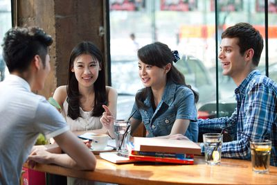 Four University Students Chatting Indoors