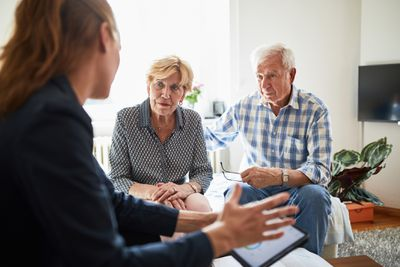 elderly couple at home meeting with an advisor