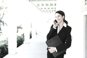 business woman talking on cell phone outside
